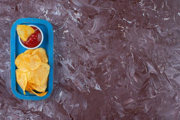 대리석 테이블에 나무 접시에 케첩과 감자 칩.