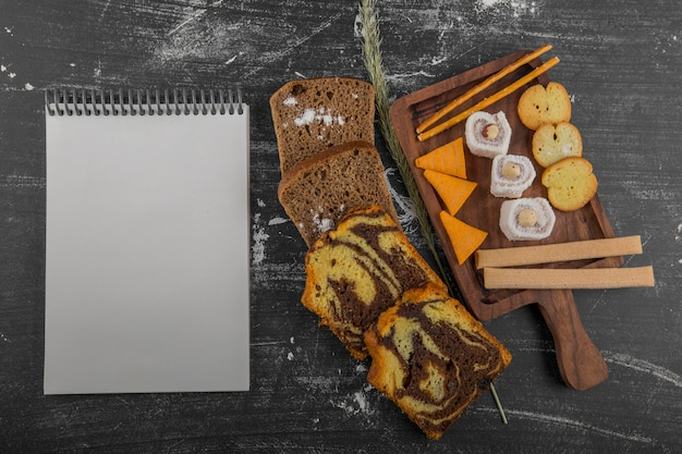 Potato chips with pastry products on a wooden platter and bread slices aside with a receipt book