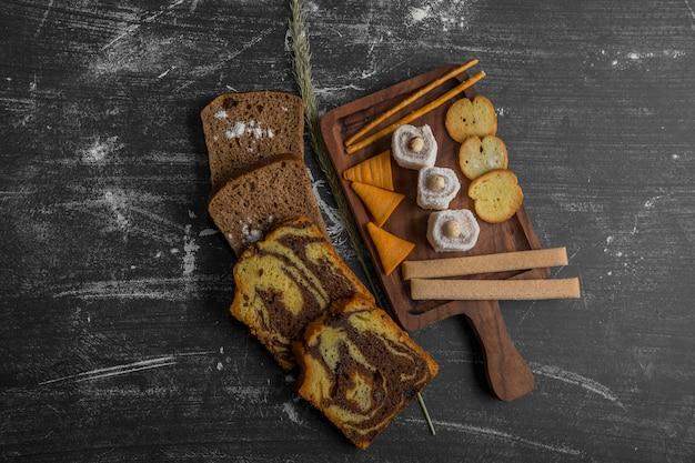 Patatine fritte con prodotti di pasticceria su un piatto di legno e fette di pane da parte