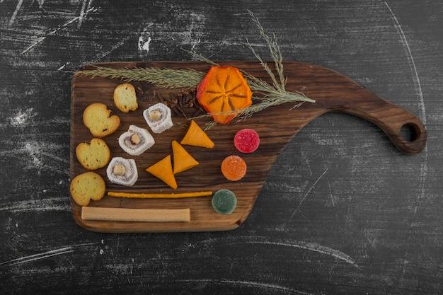 Patatine fritte con prodotti di pasticceria su un piatto di legno al centro