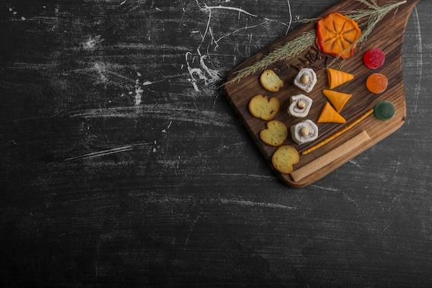 Patatine fritte con prodotti di pasticceria su un piatto di legno nell'angolo superiore