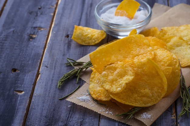 Potato chips with rosemary on wooden background