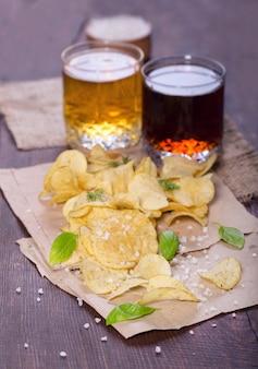 Картофельные чипсы с солью и зеленью с пивом на столе в пабе