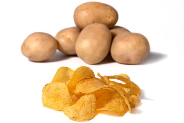 Картофельные чипсы с солью и клубнями на заднем плане на белом фоне