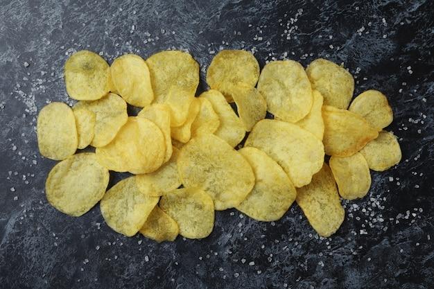 Potato chips with salt on black smokey