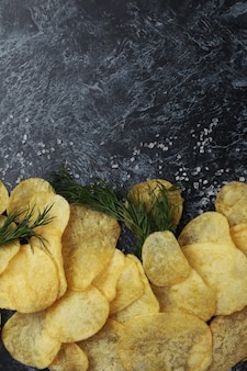 Potato chips with salt and dill on black smokey