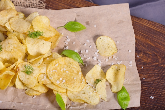 Potato chips with salt and greens on a table in a pub