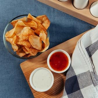 테이블에 소스와 감자 칩입니다. 수제 소스