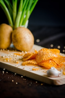 Potato chips with vegetable and garlic on a wooden chopping board