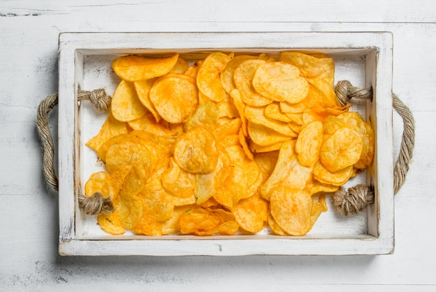 Potato chips in a wooden tray. on white rustic table.