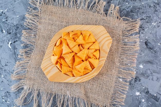 Chip di cono di patate in piatto di legno su struttura, sulla superficie di marmo