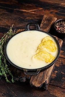 木の板の鍋にポテトチップスが入ったポテトクリームスープ。暗い木の背景。上面図。