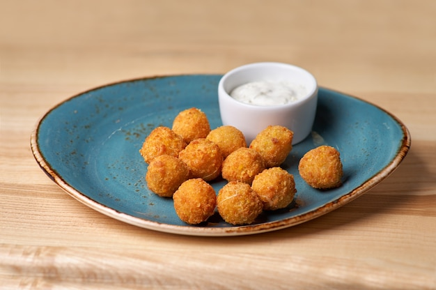 Potato croquettes. mashed potatoes balls breaded and deep fried, served with different sauce.