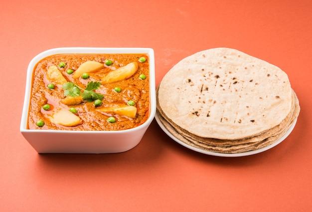 ポテトカレーまたはアルーまたはグリーンピースを添えたアールーマサラフライ、チャパティまたはロティとしても知られるフラットブレッドを添えたインドのメインコース料理、セレクティブフォーカス