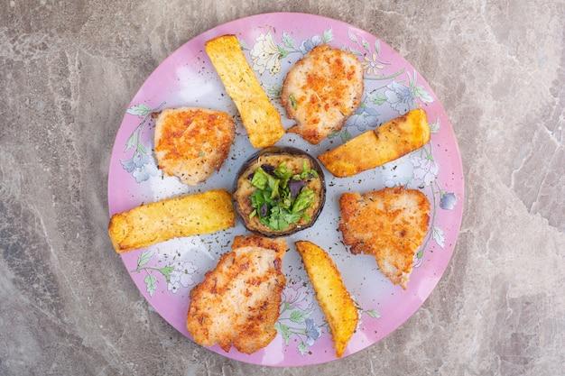 Картофель, котлеты и баклажаны на блюде, на мраморе.