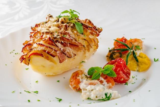 ベーコンを詰めたジャガイモを、焼き野菜と新鮮なハーブを添えた皿に盛り付けます