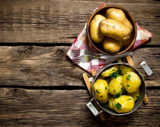 じゃがいも料理。木製のテーブルにハーブと茹でたジャガイモ。テキスト用の空き容量。上面図