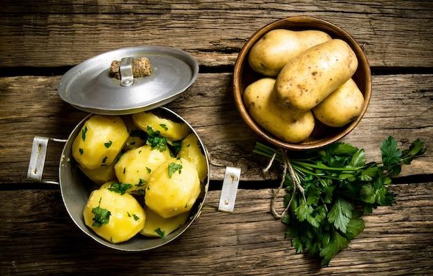 じゃがいも料理。木製のテーブルにハーブと茹でたジャガイモ。上面図