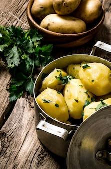 じゃがいも料理。木製のテーブルにハーブと茹でたジャガイモ。