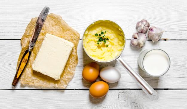 감자 음식. 으깬 감자 재료 요리 : 감자, 우유, 계란, 버터 및 기타 흰색 나무 테이블에. 평면도