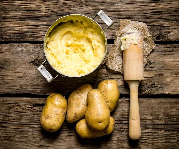 감자 음식. 나무 테이블에 유 봉과 으깬 된 감자 요리. 평면도