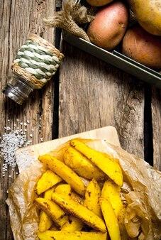 Картофельная еда. фри со специями и солью на деревянных фоне