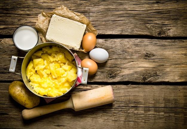 감자 음식. 으깬 된 감자 재료-계란, 우유, 버터, 감자 나무 배경. 텍스트를위한 여유 공간. 평면도