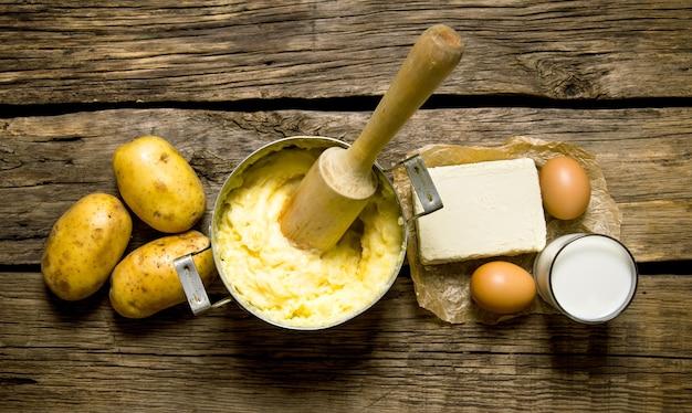 감자 음식. 으깬 감자 재료-계란, 우유, 버터 및 감자 나무 테이블에. 평면도