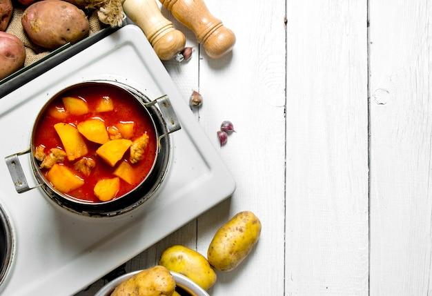 Картофельная еда. тушеный картофель с мясом и специями в электрической плите на белом деревянном столе. свободное место для текста. вид сверху
