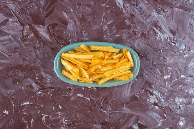 Картофель фри в тарелке на мраморе.