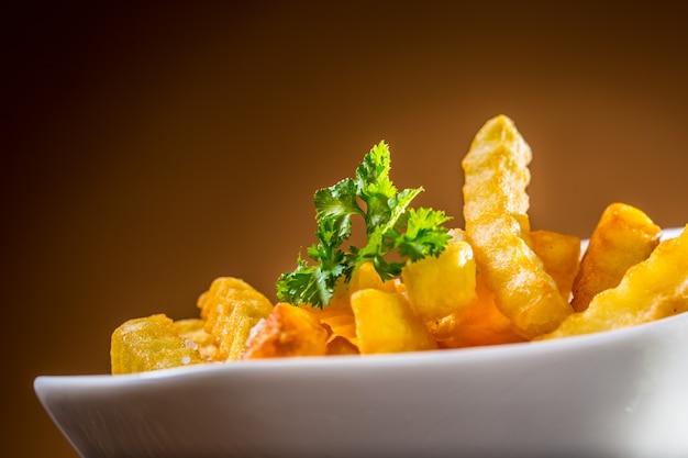 파 슬 리 허브와 함께 흰색 그릇에 감자 튀김입니다.