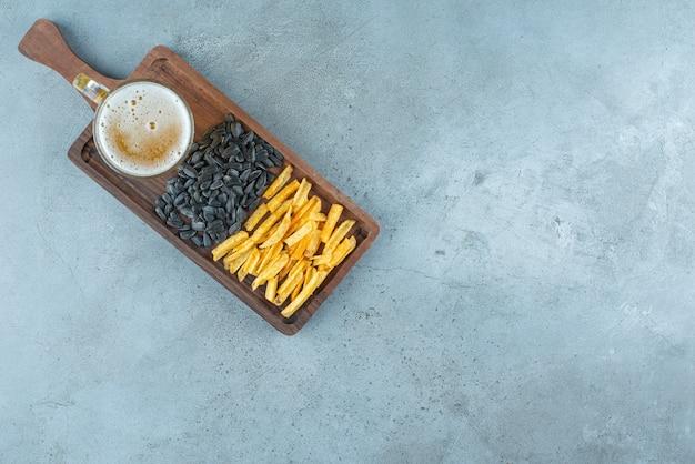 青いテーブルの上に、ボード上のポテトフライ、ヒマワリの種、ビールのグラス。