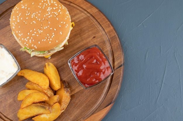 Potato fries with bowls of ketchup and mayonaisse, next to a hamburger on wooden board on blue background. high quality photo