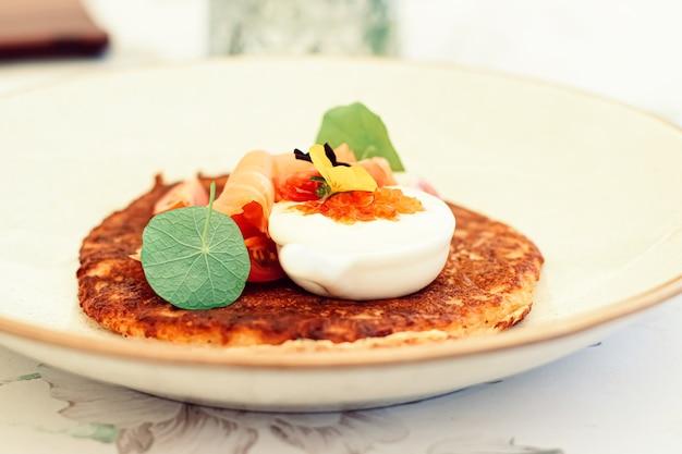 여름에 야외 고급 레스토랑에서 붉은 캐비아 연어와 사워 크림을 곁들인 감자 튀김 팬케이크