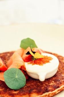 夏の屋外の高級レストランでの赤キャビアサーモンとサワークリームのポテトフリッターパンケーキ