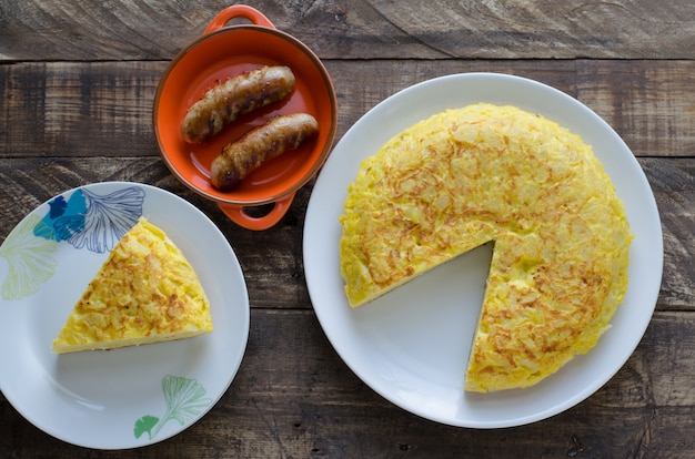 Potato omelet with grilled sausages in a clay pot.