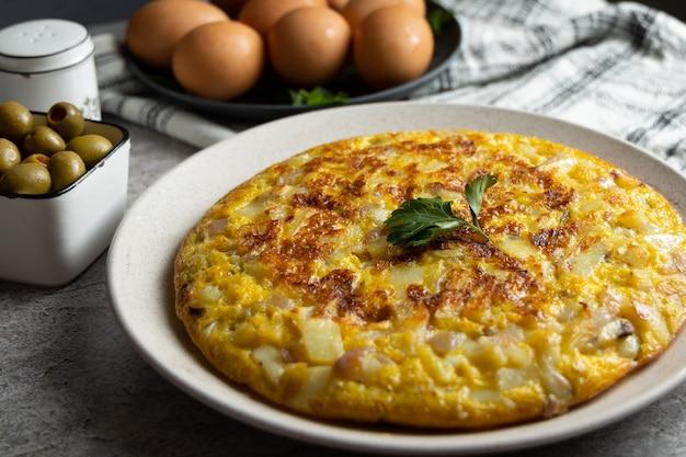 Картофельный омлет с яйцами на мраморном столе