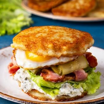 Бургер из картофельных оладий с яичницей, беконом и соленым огурцом. крупным планом