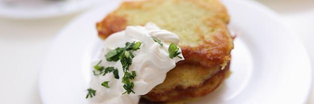 食堂のコンセプトで白いプレートダイニングに横たわっているサワークリームソースのポテトパンケーキ