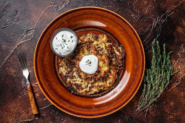 소박한 접시에 크림 소스를 곁들인 감자 팬케이크 또는 튀김