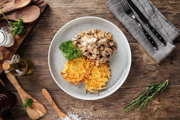 Картофельные оладьи с бефстрогановым на серой тарелке