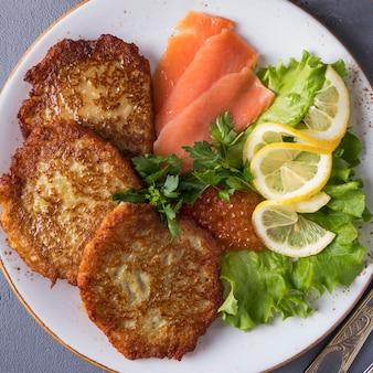 Potato pancakes with caviar and salmon.