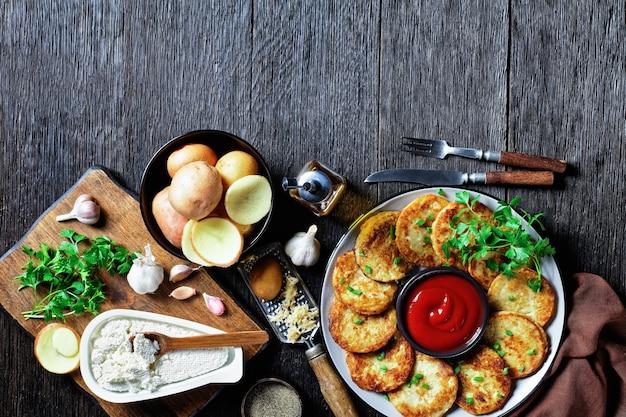 Картофельные оладьи с творогом с чесноком, петрушкой, подаются с кетчупом на тарелке на деревянном фоне, вид сверху, крупный план