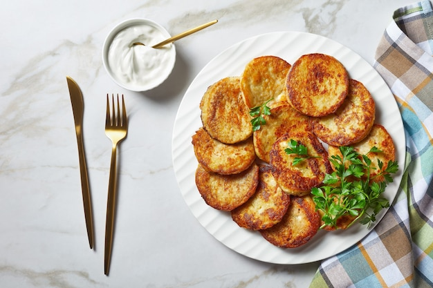 Картофельные оладьи с творогом с чесноком, петрушкой, подаются со сметанным соусом на тарелке на светлом мраморном каменном фоне с золотыми столовыми приборами, вид сверху, крупный план
