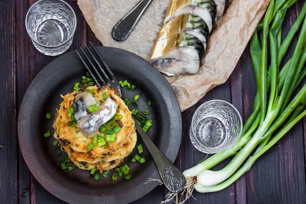 Картофельные оладьи с селедкой и луком на темном фоне