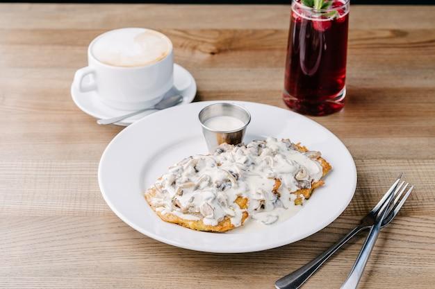 Картофельные оладьи с грибным соусом. на столике в кафе