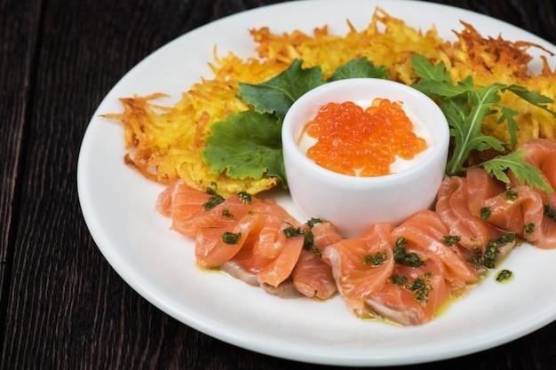 Potato pancakes with salmon fish carpacchio and red caviar