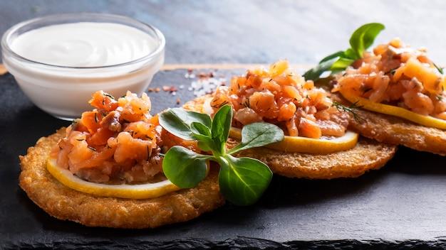 Potato pancakes with salmon and sour cream.