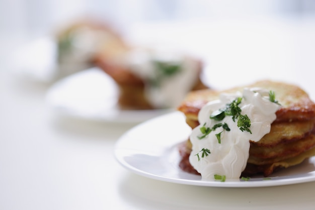 Картофельные оладьи со сметаной и зеленью на тарелке, готовя вкусный завтрак