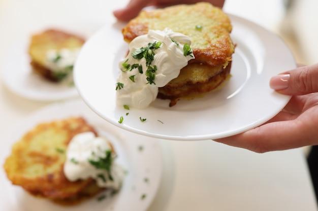 Картофельные оладьи со сметаной и зеленью на тарелке, концепция приготовления драников в домашних условиях